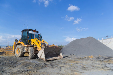 Wheel loader Excavator unloading sand with water during earth moving works at construction site