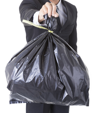 bad business: A business man arm holding a black bag of trash concept bad debt theme, bad investments, bad business Stock Photo