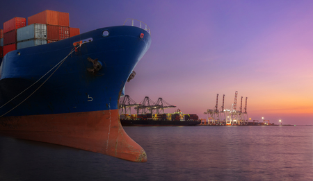 container ship in import export port of loading ship yard use for freight and cargo shipping vessel transport at twilight time. Stock Photo