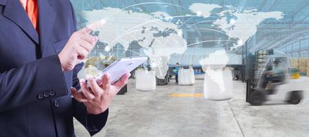 デジタル タブレット、ロジスティックのインポートおよびエクスポートについてフォーク リフトで商品をロード倉庫作業員を世界地図上のハンドプ