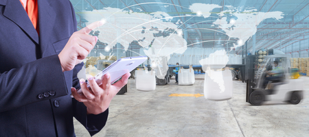 hand presses on world map with digital tablet,warehouse worker loading goods by forklift  for Logistic Import Export background