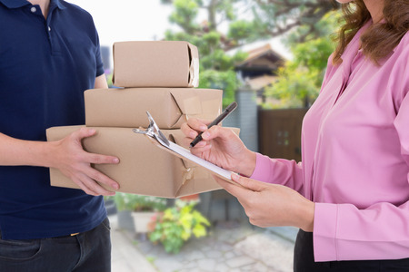 Woman signing receipt of delivery package at home.