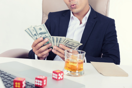Portrait of young gambling casino owner man with dollars on hand. Stock Photo