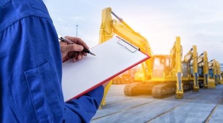 労働者は輸出入ビジネス ヤードで機械掘削機の前に文書をチェックします。