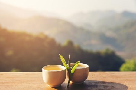 Zwei Tasse mit Teeblatt auf Tisch über Gebirgslandschaft mit Sonnenlicht. Schönheit Natur Hintergrund.