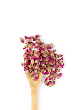 Flower tea rose buds with wooden spoon isolated on white background - flowers and plants. Stockfoto