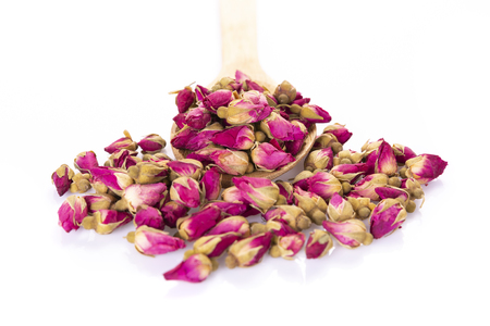 Flower tea rose buds with wooden spoon isolated on white background - flowers and plants. Фото со стока