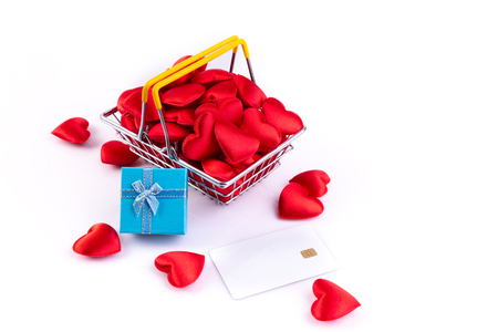 red hearts with credit card and gift box in shopping basket, valentines day background Stock Photo