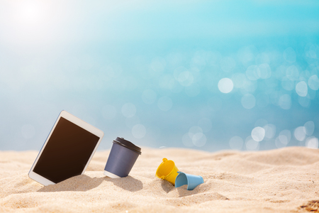 coffee paper cup and tablet on beach - Summer Holidays