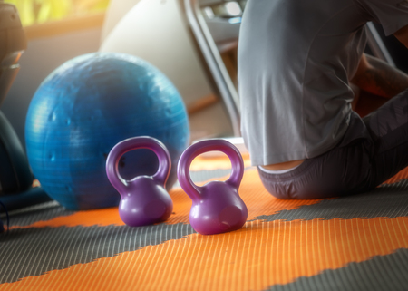 The young man was sitting and resting after exercise with a dumbbell in the gym. Stockfoto