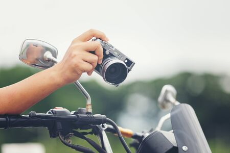 Young Asian male traveler and photographer sitting on the classic style racer motorbike holding camera  taking photo on road, Travel photography concept