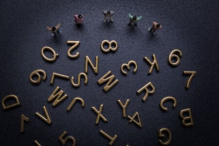 Miniature people: Group of small businessmen looking alphabet. Top view. 스톡 콘텐츠