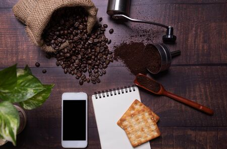 Coffee beans and ground powder  with smartphone on wooden background