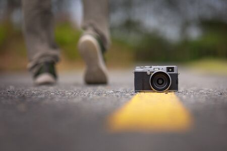 Camera on the road with photographer background, travel concept