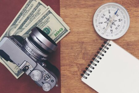 Vintage camera with paper note on wooden table.Budget plan travel concept.