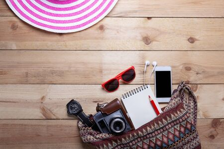 Top view of equipment hipster young lady or girl on vacations. Womans summer holidays accessories composed on wooden background.