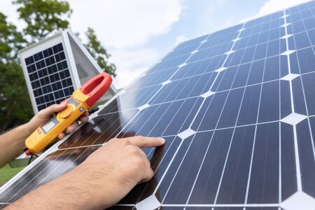 Engineer solar photovoltaic panels station checks with measurement tool.
