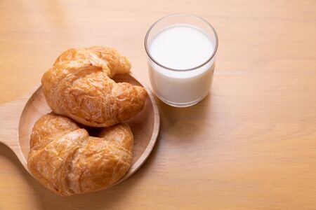 freshly baked croissants and milk cup on table.