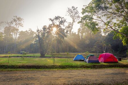 Tourists tents at grass field for camping trip at sunrise