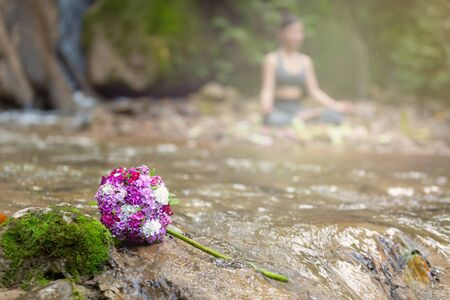 Beautiful bouquet with woman sitting in yoga pose in front of waterfall as a background.