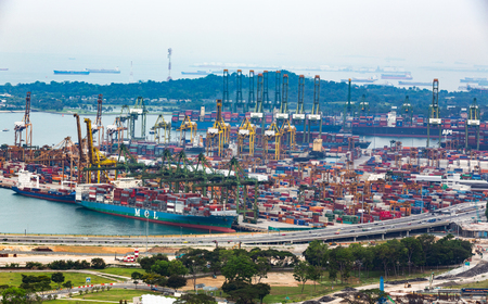 Logistics containers at commercial port with buildings in high view.