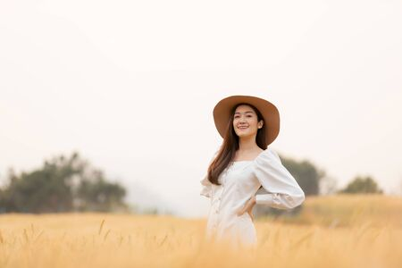 Young woman walking in barley field with hat up and having fun. summer vacation.
