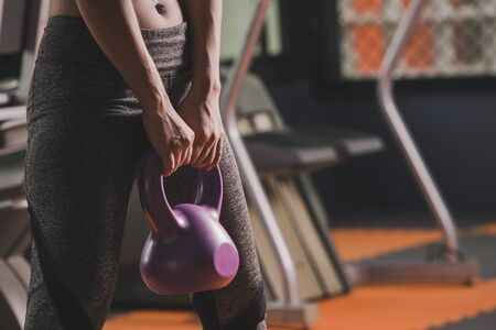 Sport woman fit kettlebell training in gym room. sport relax and healthy life in indoor or sport complex to add strength to the lungs.