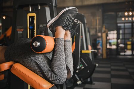Close up view gym seated leg curl machine exercise woman at indoor.Health concept.
