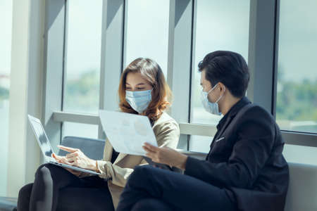 Business workers discussing business marketing and wearing medical face mask for social distancing in new normal situation for virus prevention. 스톡 콘텐츠