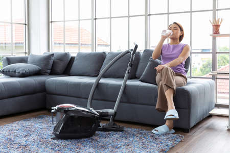 Beautiful young Asia woman drinking water after  cleaner while cleaning floor in the livingroom at home.Housekeeping occupation concept. 写真素材