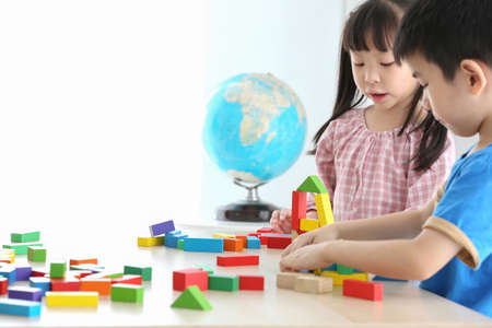 Asian preschool student build block toys at home or daycare. Cheerful kid playing with colour cubes. Educational toys for preschool and kindergarten children. Imagens