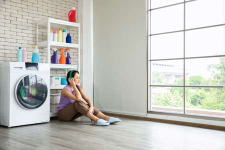 Young Asia woman sitting near washing machine wash and listening music for waiting her clothes at laundry room. Banque d'images