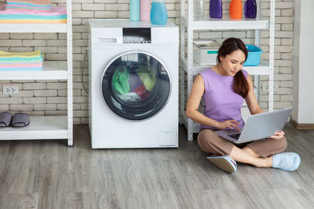 Woman sitting near washing machine wash for working on laptop at home her clothes at laundry room.