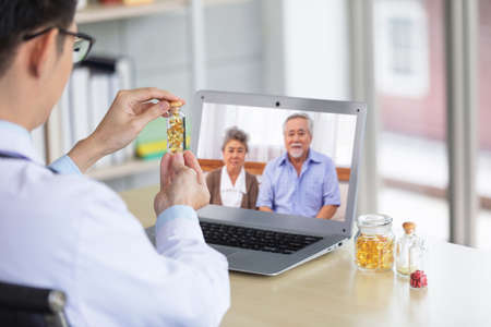 Concentrated doctor working on line with a laptop sitting in a desk in a consultation abouth cod liver oil for senior couple.Social distancing or new normal style. Stock Photo