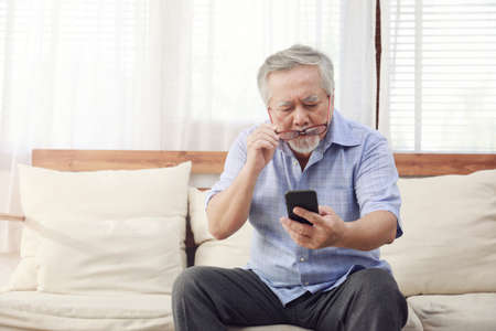 Older men move glasses down to look at the phone in the hand due to long sighted problems, which makes vision difficult.Health problems of the elderly. Banque d'images