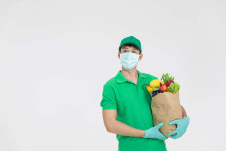 The smart food delivery service man in green uniform wearing face mask handing fresh food to recipient for customer is shopping on line order .Express delivery, food delivery, online shopping concept.