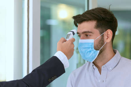 Body temperature check,Receptionist and guest wearing face mask at front desk while having conversation at hotel.Covid 19 and coronavirus infection protection and protective policy concept .