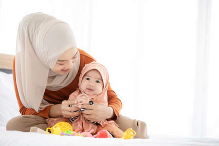 A Muslim mother and toddler are indoors in their bedroom. The mother is wearing a head scarf, and she's sitting on the bed while holding her baby and they are both smiling.
