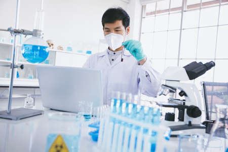 Young Asia male scientist making notes with result of  blood carrying out researches on COVID-19 vaccine in laboratory.