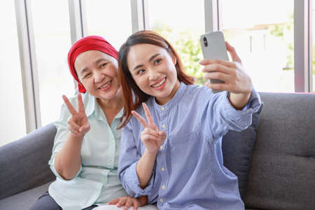 A senior woman with cancer wearing a headscarf relaxes at home with her adult daughter and take picture by smartphone in the living room.The women are full of hope for the future.