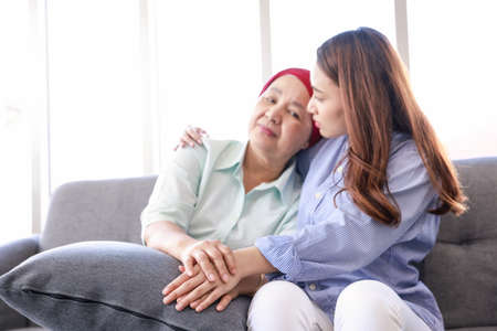 Young Asia woman with her mother wearing a headscarf  fighting cancer sits on the couch  and her arm wrapped around her mother, and they're both looking out the window in a quiet moment of contemplation. Stok Fotoğraf
