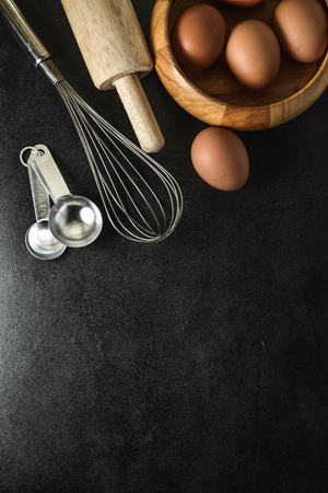 baking ingredients: Kitchen utensils and baking ingredients: egg and flour on black background, copy-space.