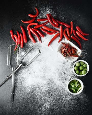 Red Hot Chili Peppers on dark background with flour, Copy-space background.