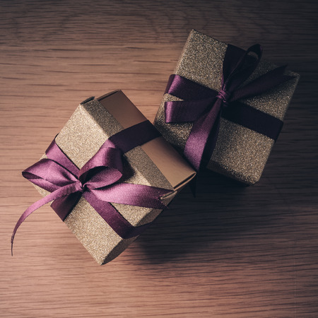 purple ribbon: Christmas presents with purple ribbon on dark wooden background