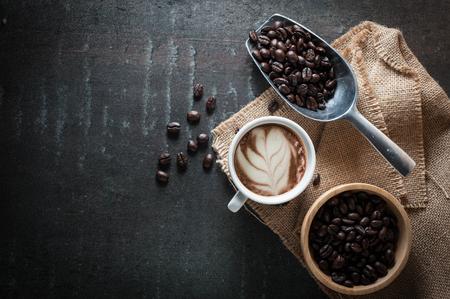 Taza de café con café en grano sobre fondo de piedra negra