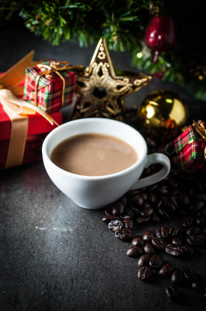 crema: Coffee cup and christmas toys with pine brench on black stone background . Stock Photo