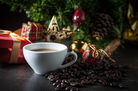 Coffee cup and christmas toys with pine brench on black stone background . Stock Photo