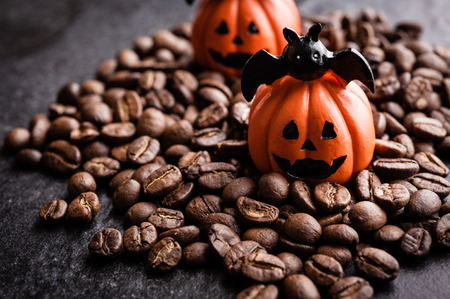 Halloween pumpkin decoration with coffee beans on dark background Stock Photo