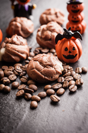 Eclairs and coffee beans with halloween decoration on black background Stock Photo