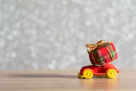 Toy Car with Christmas tree and gift box. Christmas landscape with gifts and snow. Merry christmas and happy new year greeting card with copy-space. Christmas celebration holiday background. Stock Photo